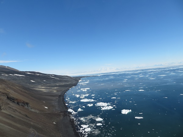"View of part of the ""precarious area"" on our way to Cape Bird. This is looking back toward McMurdo. You can see the elevation is steep along the coast, and there is plenty of open water. Mt Erebus is out of view but to the front left."