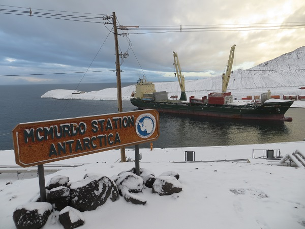 """McMurdo Station Antarctica,"" the Vessel, and snow-capped Hut Point behind it."