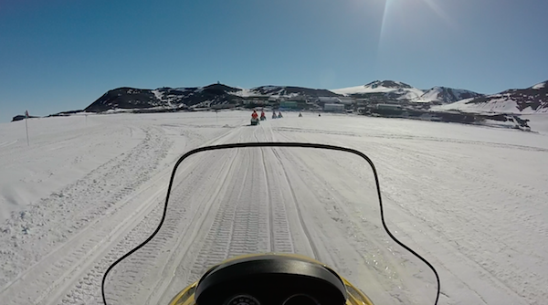 Snowmobiling with McMurdo station in background