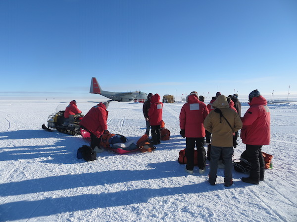 We passengers wait for the go-ahead to board the Herc. That's Jim laying on a sled, being pulled by the snowmobile.